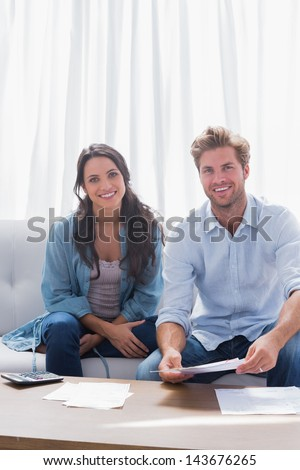 Couple smiling while doing their accounts sat in a couch - stock photo