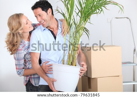 Couple smiling with plant - stock photo