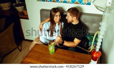 couple smoking hookah talking and laughing in the shisha bar - stock photo
