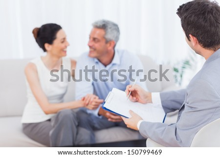 Couple speaking while salesman is holding contract on couch at home - stock photo