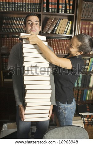 Couple stacking books under a man's chin. Vertically framed photo - stock photo