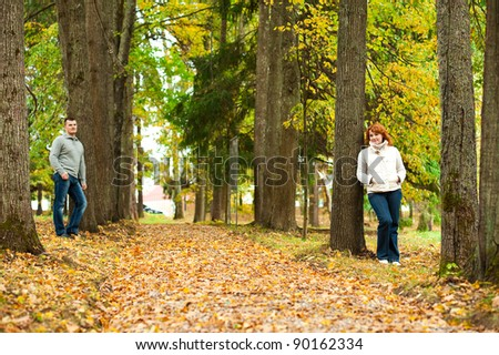 Couple stand leaning against a tree in autumn park