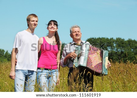 couple stand near grandfather with accordion in field near wood, close eyes - stock photo