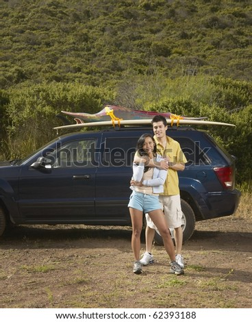 Couple standing alongside car on road trip - stock photo