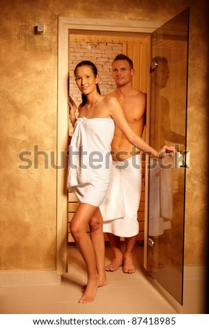 Couple standing at sauna door, smiling after relaxing in steam, leaving.? - stock photo
