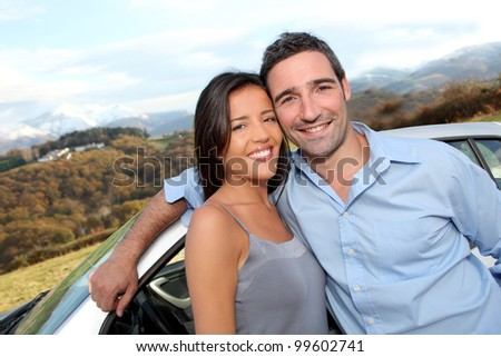Couple standing by car on the road