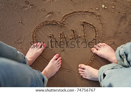 couple standing by heart with initials scratched into beach - stock photo