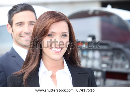 Couple standing by the cockpit of a light aircraft - stock photo