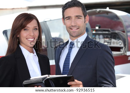 Couple standing by the cockpit of a light aircraft