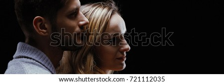 Couple standing close and hugging each other against black background