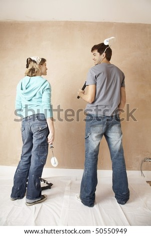 Couple standing, holding paint rollers in unrenovated room, back view - stock photo