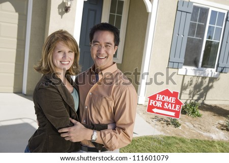 Couple standing in front of a new home - stock photo