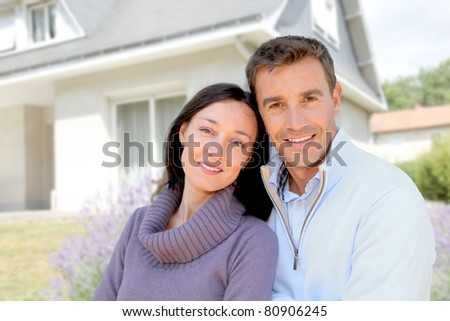 Couple standing in front of new home
