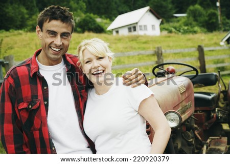 Couple standing in front of tractor - stock photo