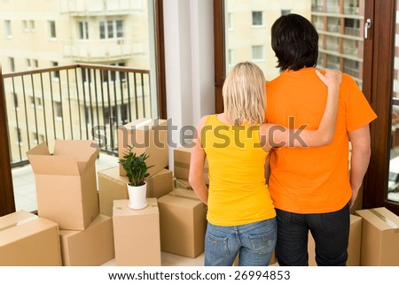 Couple standing in new house - stock photo