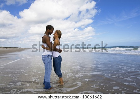Couple standing in water, holding each other - stock photo