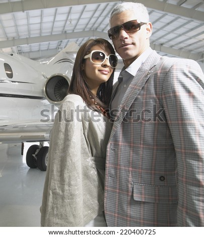Couple standing next to airplane in hanger - stock photo