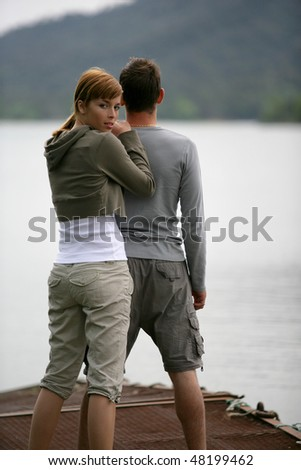 Couple standing on a pontoon by a lake - stock photo