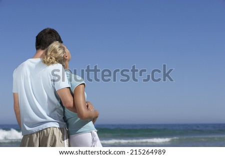 Couple standing on beach, looking at horizon over sea, man embracing woman, rear view - stock photo