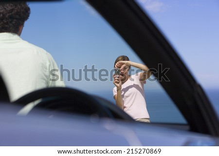 Couple standing on clifftop overlooking Atlantic Ocean, woman photographing man beside car - stock photo