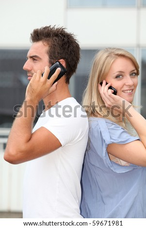Couple standing outside with mobile phone - stock photo