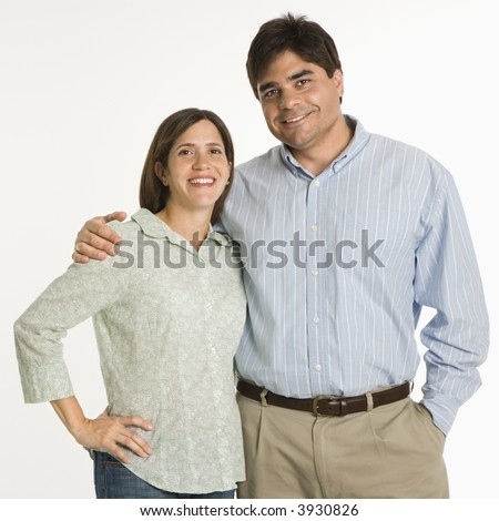Couple standing smiling against white background. - stock photo