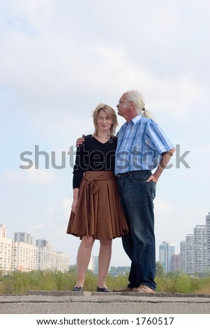 Couple standing together against cityscape
