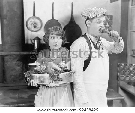 Couple standing together in a kitchen with a cooked turkey - stock photo