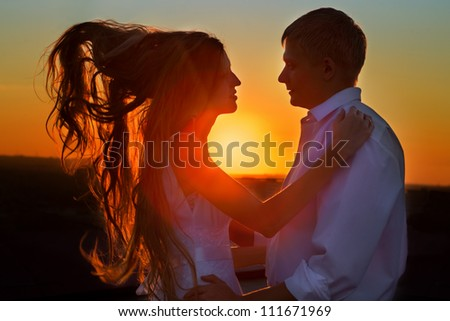 Couple standing with amazing sunset in backdrop