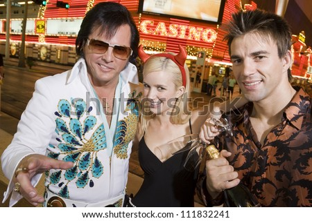 Couple standing with Elvis impersonator