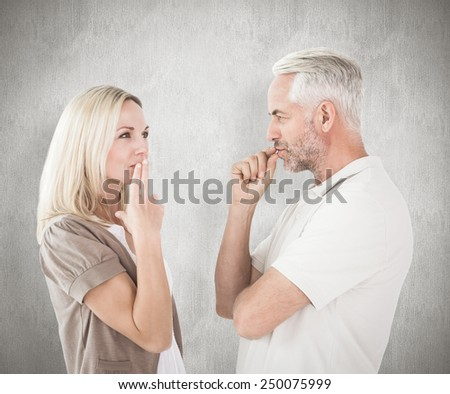Couple staying silent with fingers on lips against weathered surface