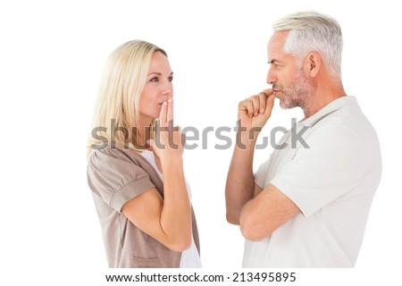 Couple staying silent with fingers on lips on white background - stock photo