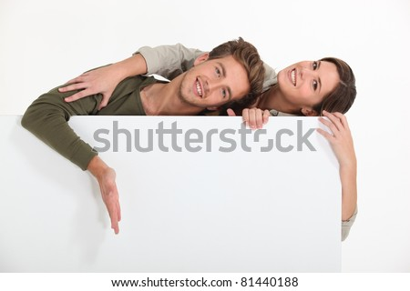 Couple stood by blank message board - stock photo