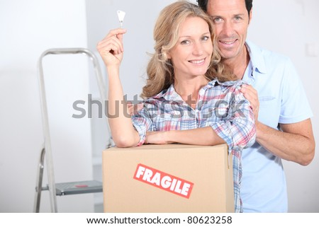 Couple stood by packing boxes - stock photo