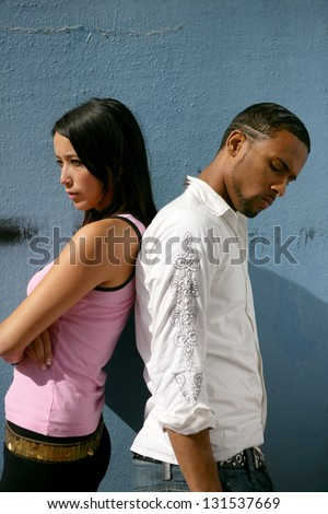 Couple stood by wall having an argument - stock photo