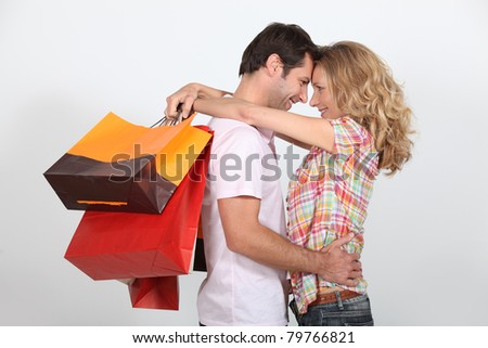 Couple stood facing each other holding shopping bags - stock photo