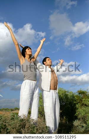 Couple stood in a field with their arms raised - stock photo