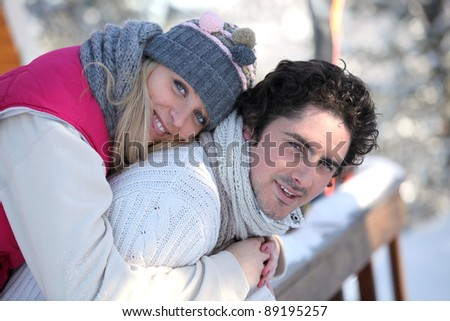 Couple stood on chalet decking - stock photo