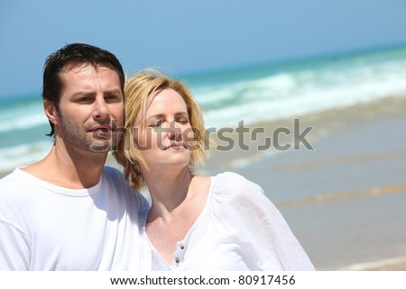 Couple stood together on a  beach - stock photo