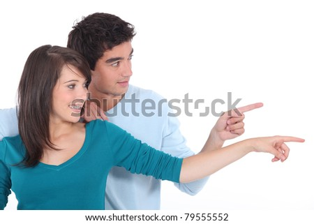 Couple stood together pointing into the distance - stock photo
