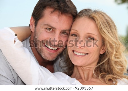 Couple stood with arms around each other - stock photo