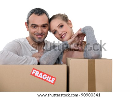 Couple stood with storage boxes - stock photo
