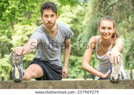 Couple stretching legs after run outdoors- Young athletes getting warm for a run in the park - stock photo