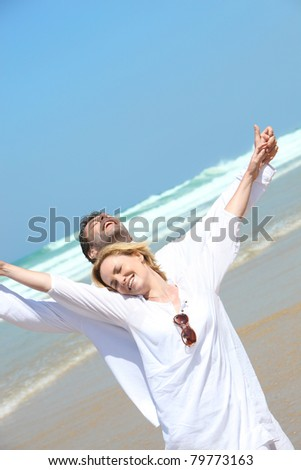 Couple stretching on the beach - stock photo