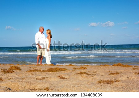 couple strolling around at the beach gazing into the deep blue sea in South Florida. - stock photo