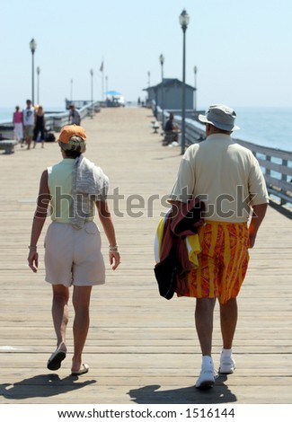 Couple strolls on pier. - stock photo