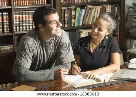 Couple studies in library. There are books and tools on the table and they are smiling. Horizontally framed photo. - stock photo