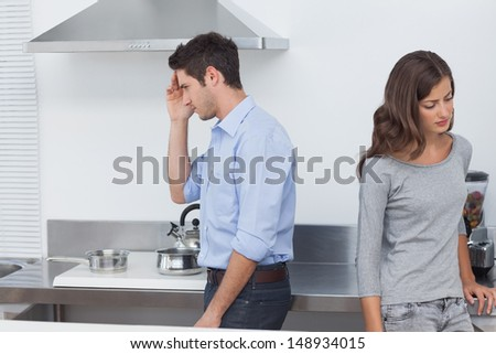 Couple sulking at each other in the kitchen after a dispute - stock photo