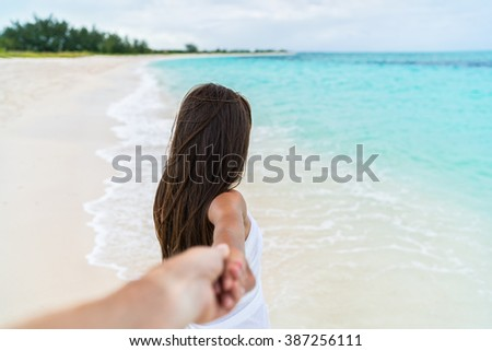 Couple summer vacation travel - Woman walking on romantic honeymoon beach holidays holding hand of boyfriend following her, view from behind. POV. - stock photo