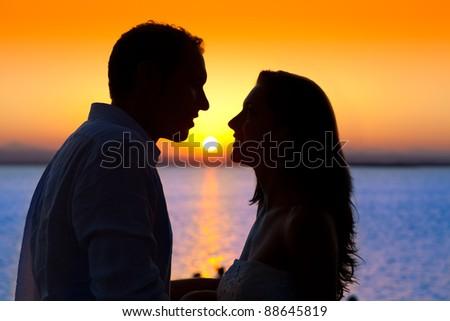 couple sunset profile back light in orange sea lake - stock photo
